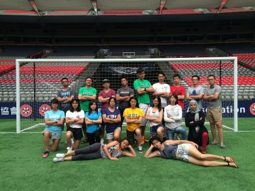 group of students posing in front of soccer net